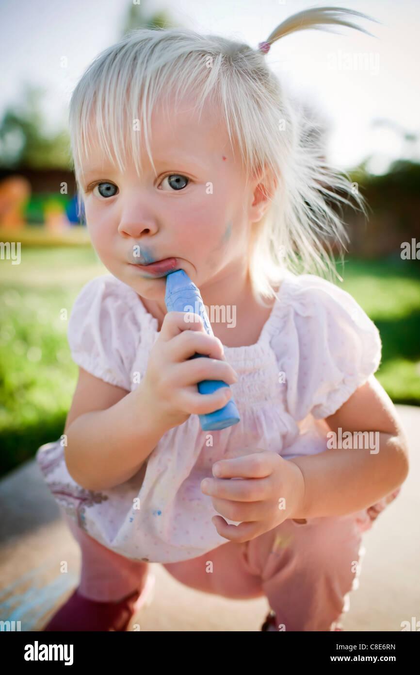 Kleinkind Mädchen Zeichnung im Gesicht mit Sidewalk Chalk Stockbild