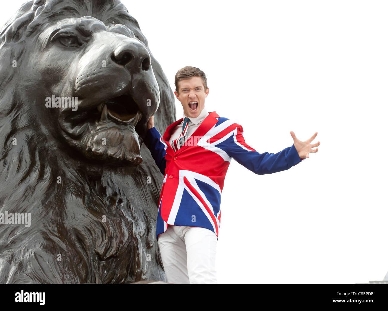 Junger Mann mit Union Jack jacket Brausen neben dem Lion Statue, Trafalgar Square, London, England Stockbild