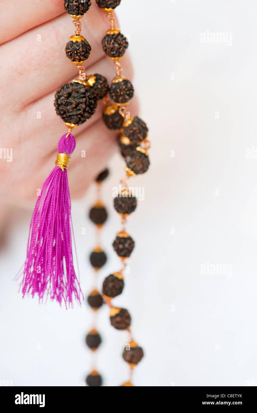 Mans Hand mit indischen Rudraksha / Japa Mala Gebet gegen weiße Perlen Stockfoto