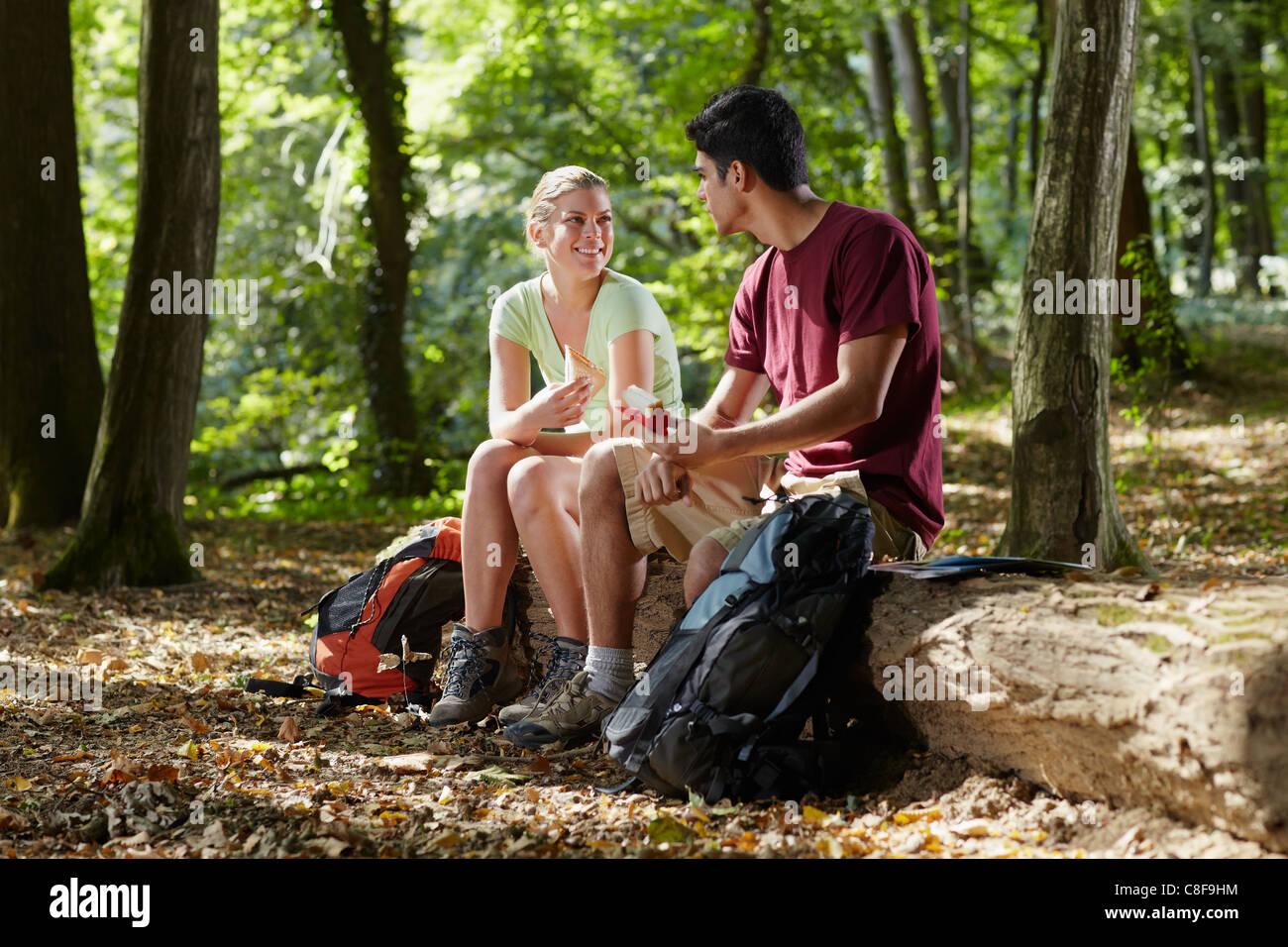junger Mann und Frau zu Mittag mit Sandwich während Wandern Ausflug. Horizontale Form, in voller Länge Stockbild