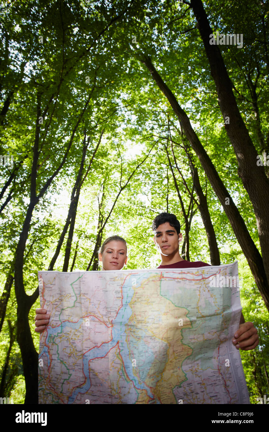 junger Mann und Frau Überprüfung Karte während Wandern Ausflug und suchen Sie nach Reiseziel. Vertikale Stockbild