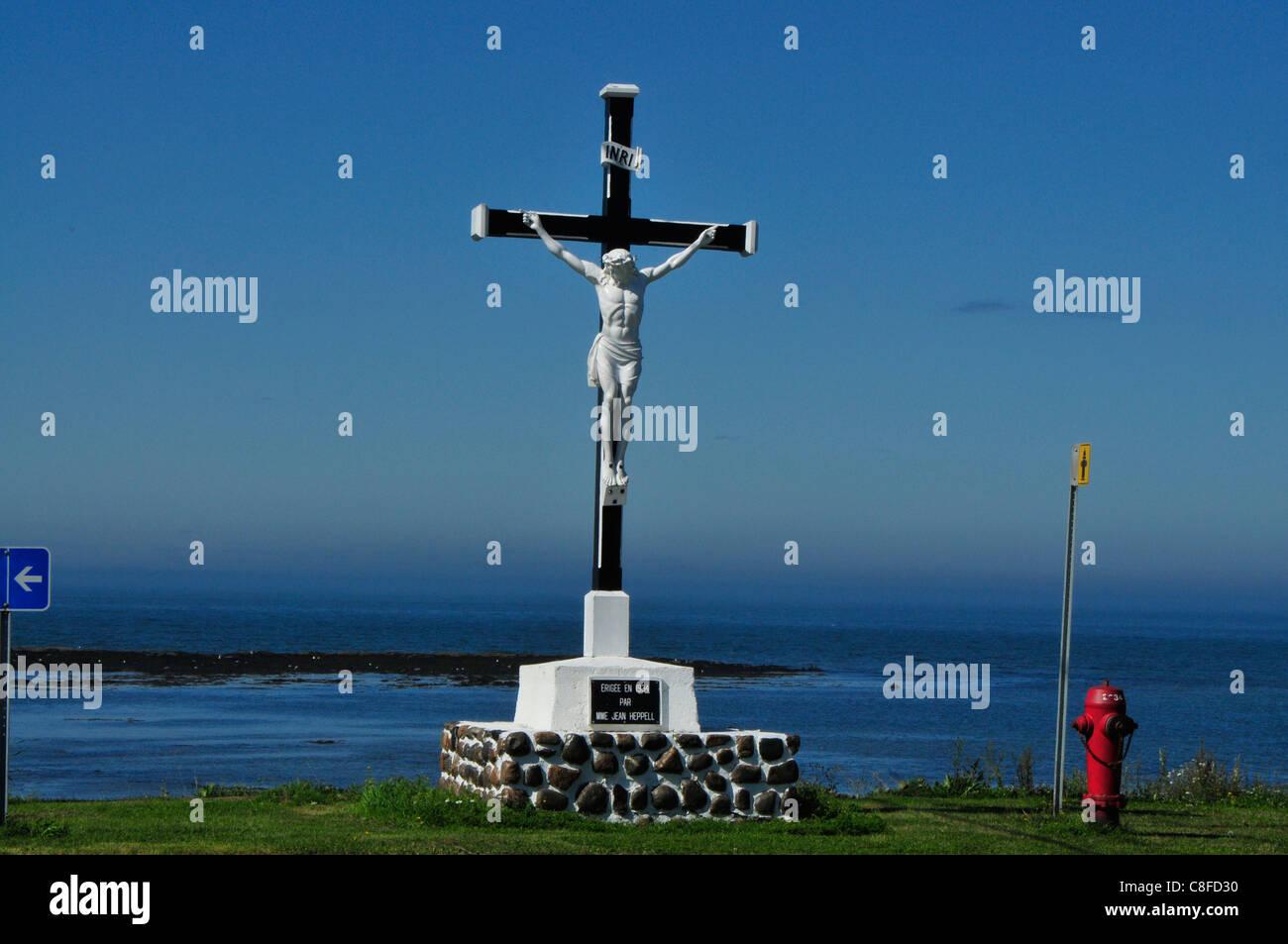 Ein am Wegesrand Kruzifix mit Blick auf die Küste der Region Saguenay von Quebec, Kanada. Stockbild