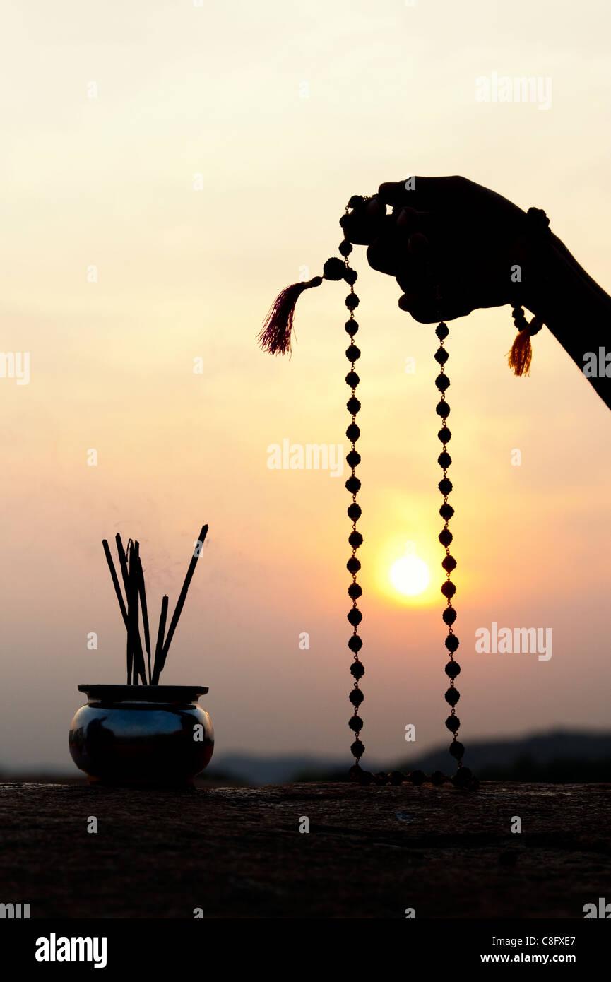 Mans Hand mit indischen Rudraksha / Japa Mala Gebet Perlen und Weihrauch. Silhouette Stockfoto