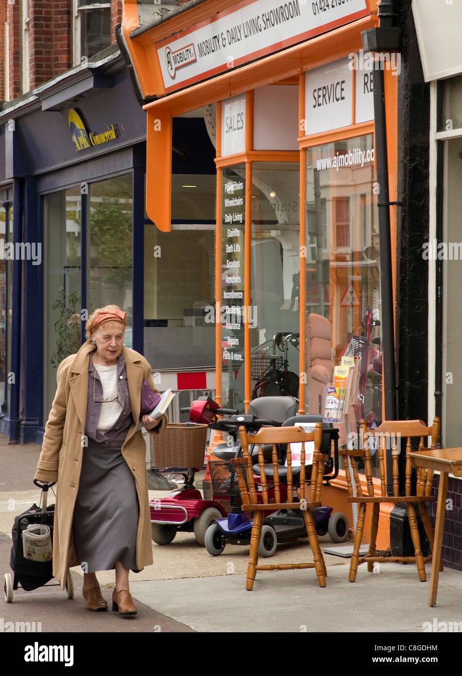ältere Frau, vorbei an einem kleinen shop Verkauf Scooter und nützliche Geräte für ältere Stockbild