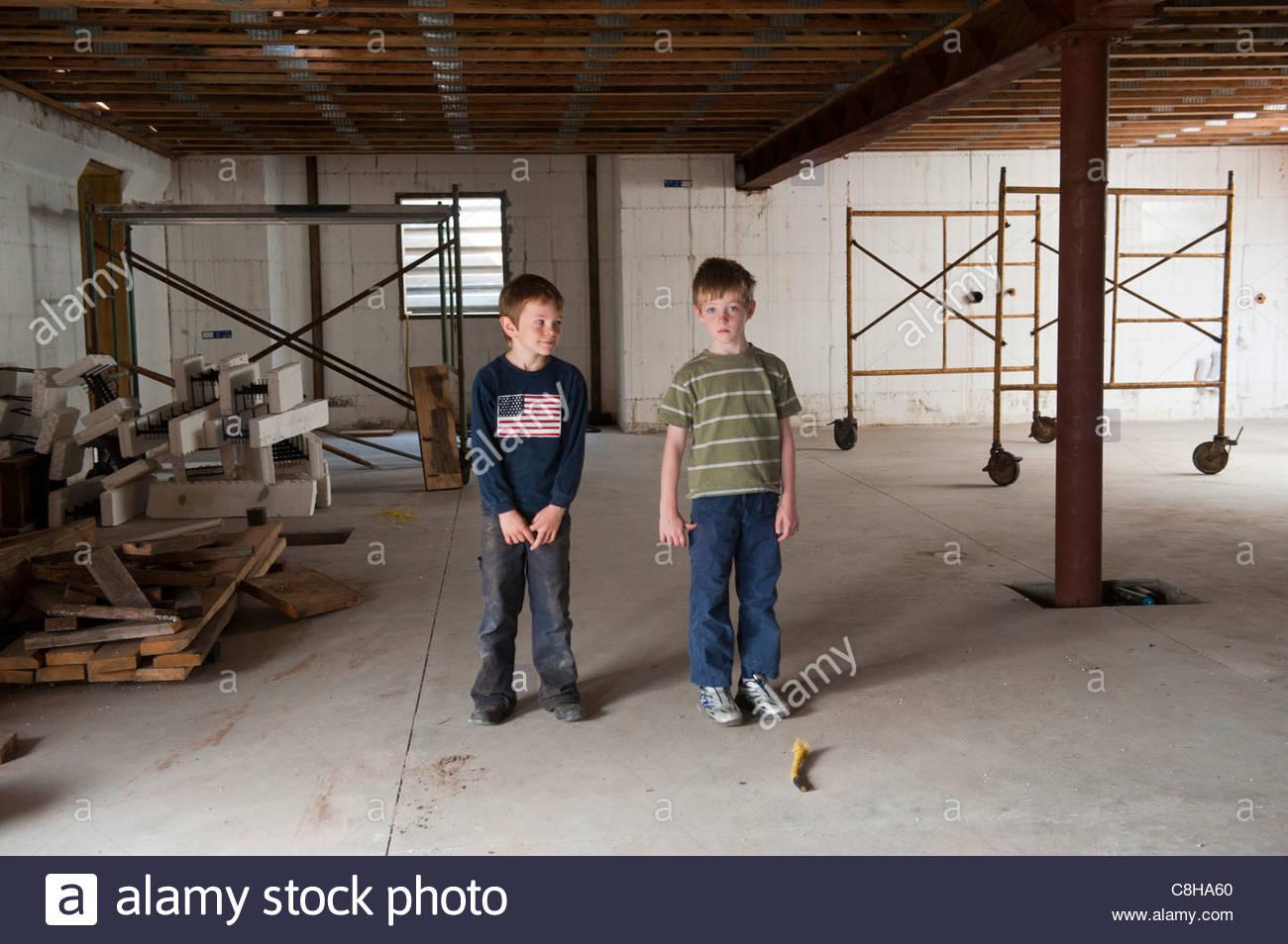 Zwei Jungs Im Keller Eines Hauses Im Bau.