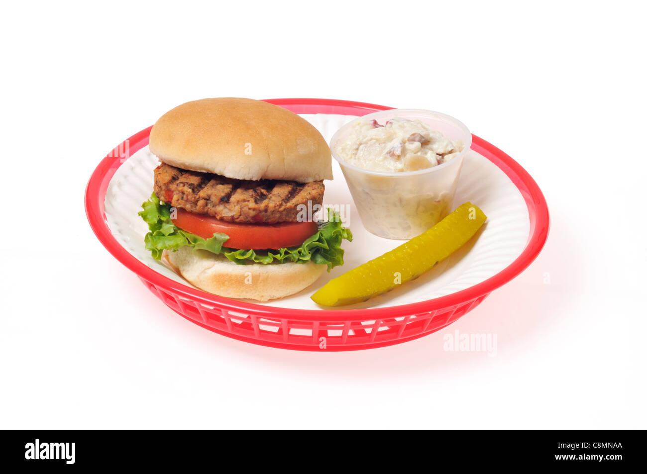 Veggie-Burger mit Salat und Tomate in Brötchen in einem roten Retro-Kunststoff-Korb auf weißem Hintergrund, Stockbild