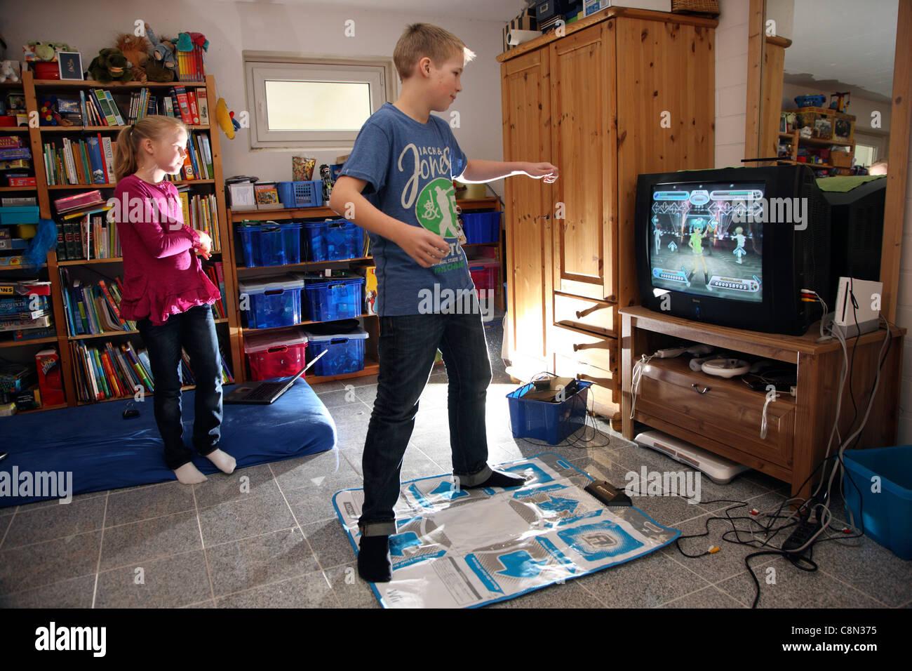 zwei kinder 10 m dchen und jungen alter von 13 jahren zu hause mit einem wii videospiel zu. Black Bedroom Furniture Sets. Home Design Ideas