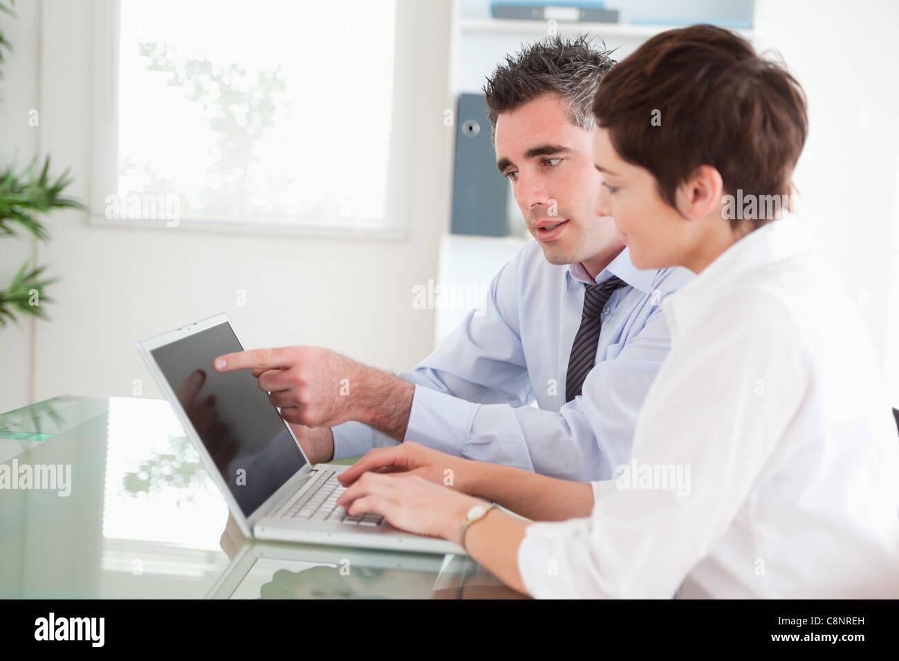 Mann zeigte sich etwas auf seine Sekretärin auf einem notebook Stockfoto
