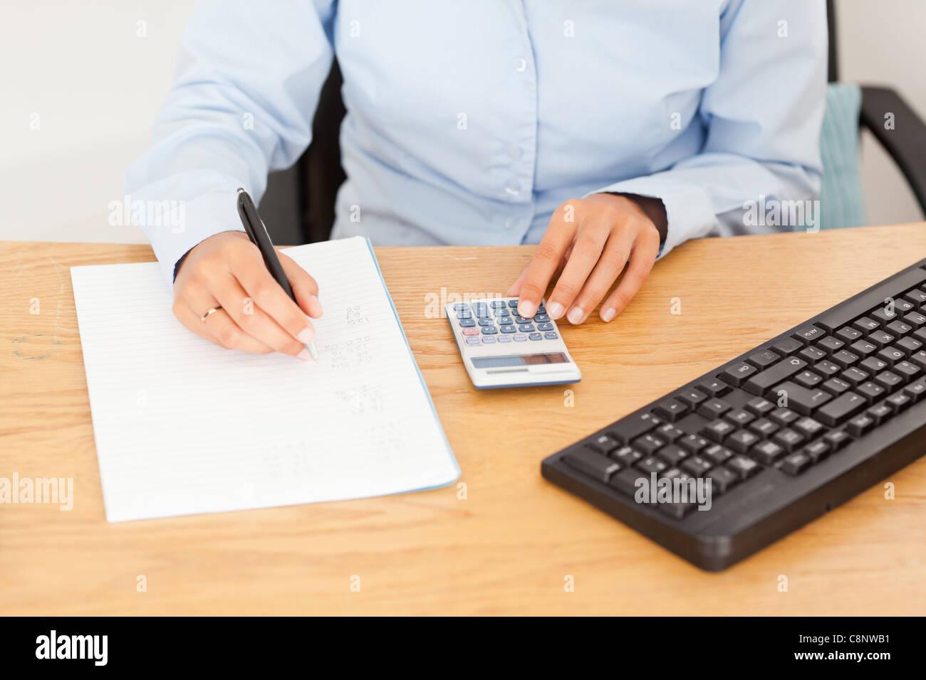 Weibliche Buchhalter Ergebnisse auf ein Stück Papier zu schreiben Stockbild
