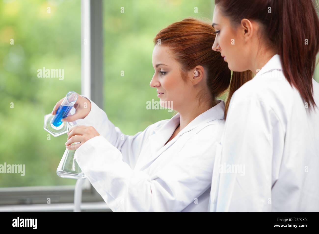 Junge Wissenschaftler, die Flüssigkeit in einen Erlenmeyerkolben gießen Stockbild
