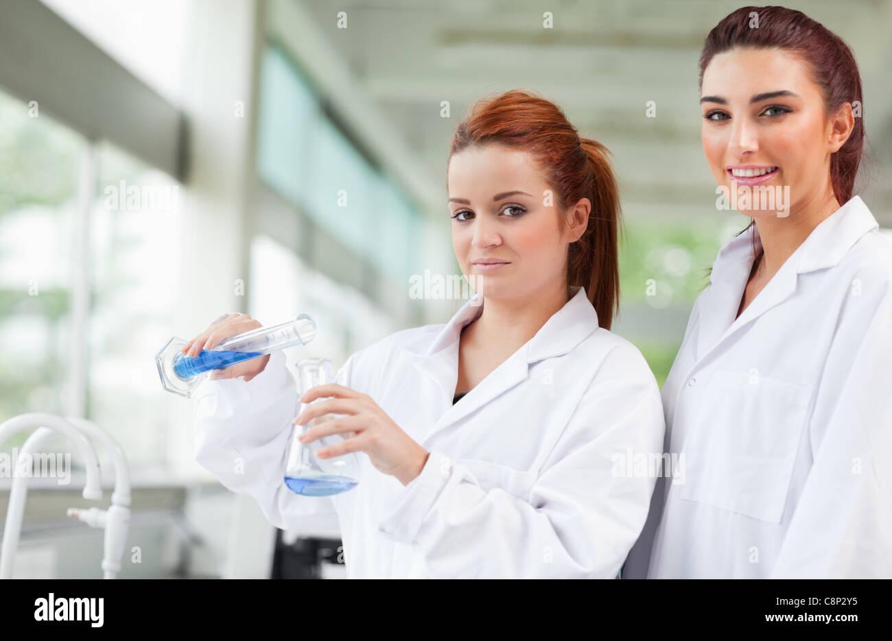 Wissenschaftler, die blaue Flüssigkeit in einen Erlenmeyerkolben gießen Stockbild