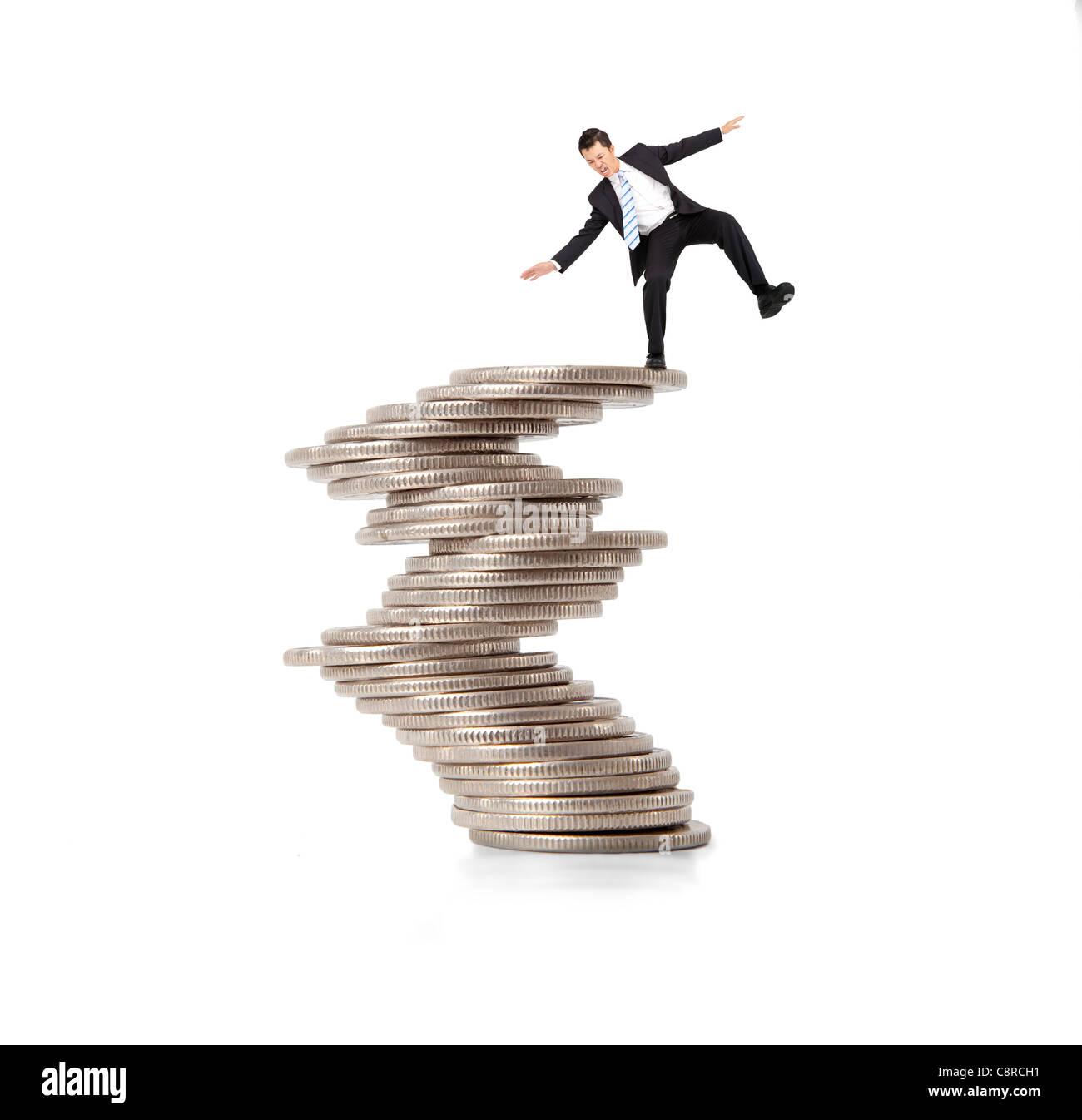 Finanz- und Krisenkonzept. Geschäftsmann, stehen auf den instabilen Münzen Stockbild