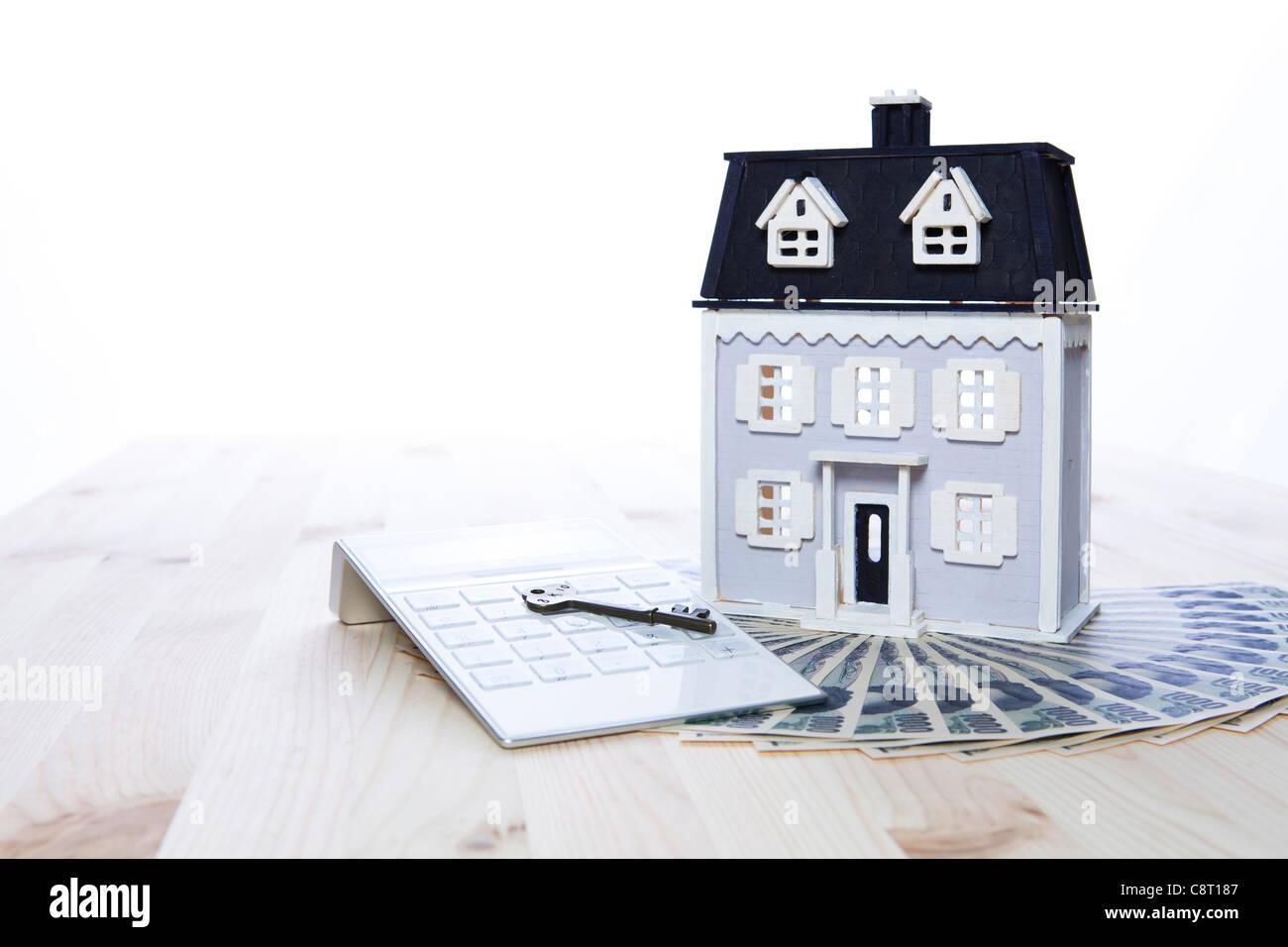 Modell Haus auf Papierwährung mit Taschenrechner und Schlüssel Stockbild