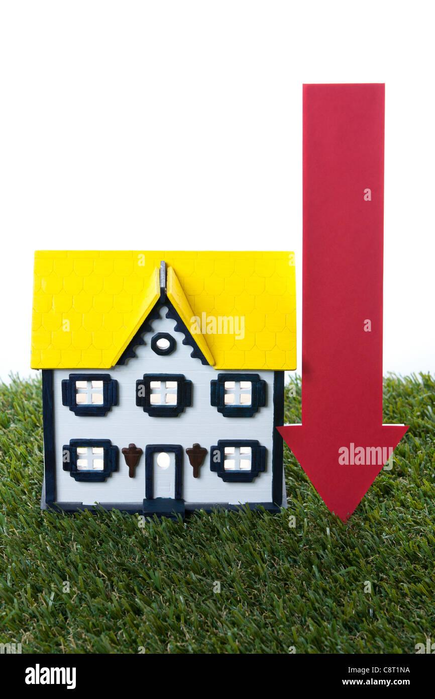 Modell des Hauses auf dem Rasen mit nach unten weisenden Pfeil Schild vor weißem Hintergrund Stockbild