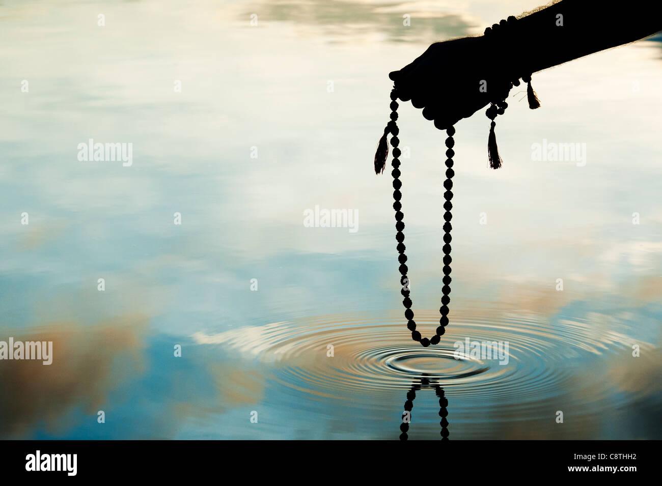 Hand, die indischen Rudraksha / Japa Mala Gebet Perlen über Plätschern des Wassers. Silhouette Stockfoto