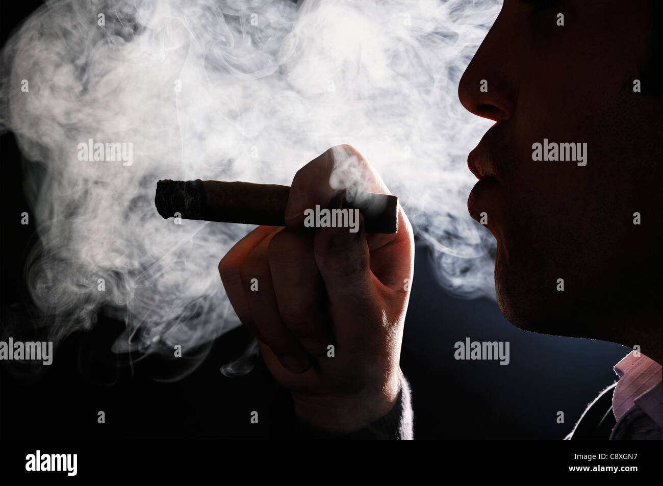Man raucht eine Zigarre Stockbild