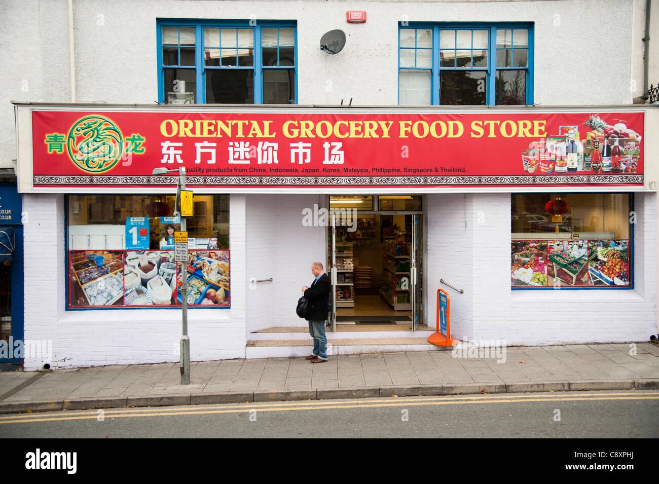 ein Mann, der außerhalb einer orientalischen chinesische Lebensmittel Lebensmittelgeschäft, Bangor Wales Stockbild
