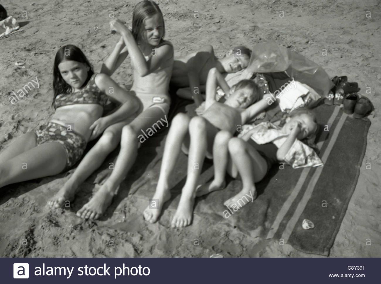 Alle zusammen ausruhen und Sonnen nach einem Bad Holland 1960er Jahre Stockbild