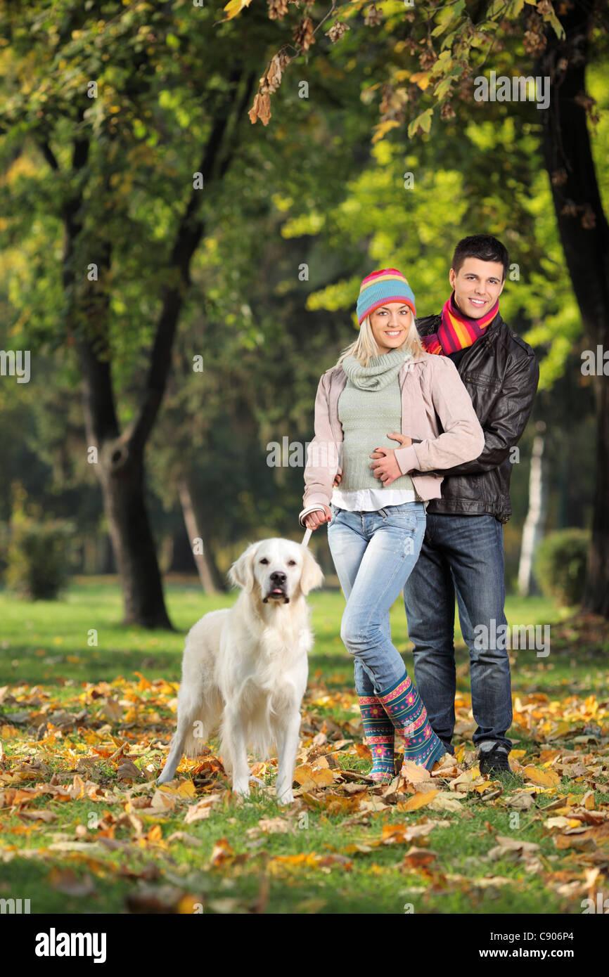 Ein Lächeln auf den Lippen Ehepaar und ihr Hund posiert im Park im Herbst Stockfoto