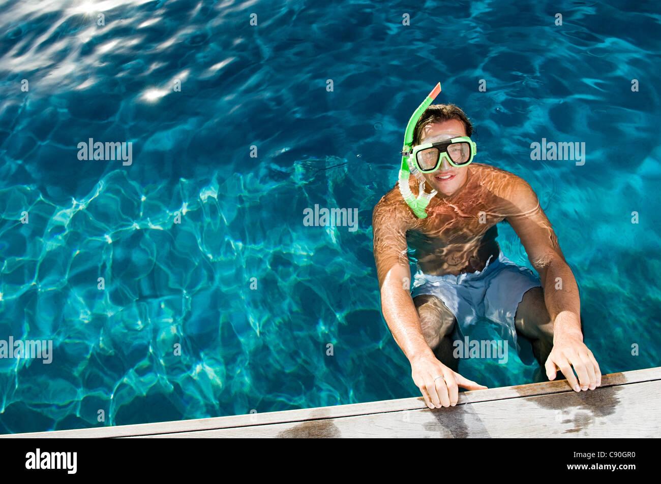 Junger Mann mit Schnorchel am Pool, hoher Winkel Stockbild