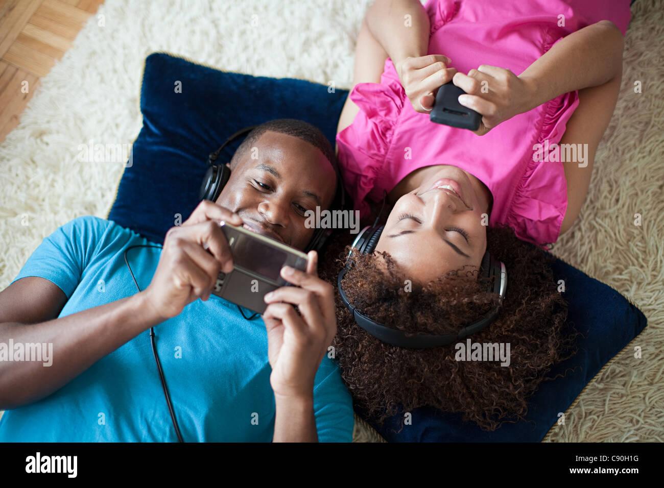 Mann und Frau auf dem handheld-Gerät und Smartphone spielen Stockbild
