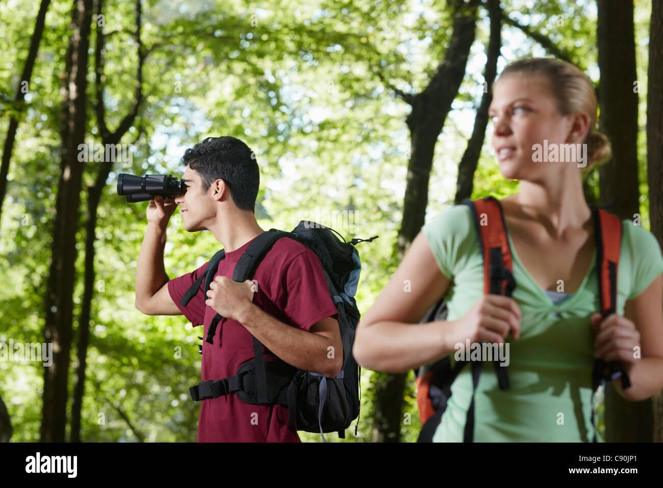Junge menschen unter bäumen wandern und vögel mit dem fernglas zu