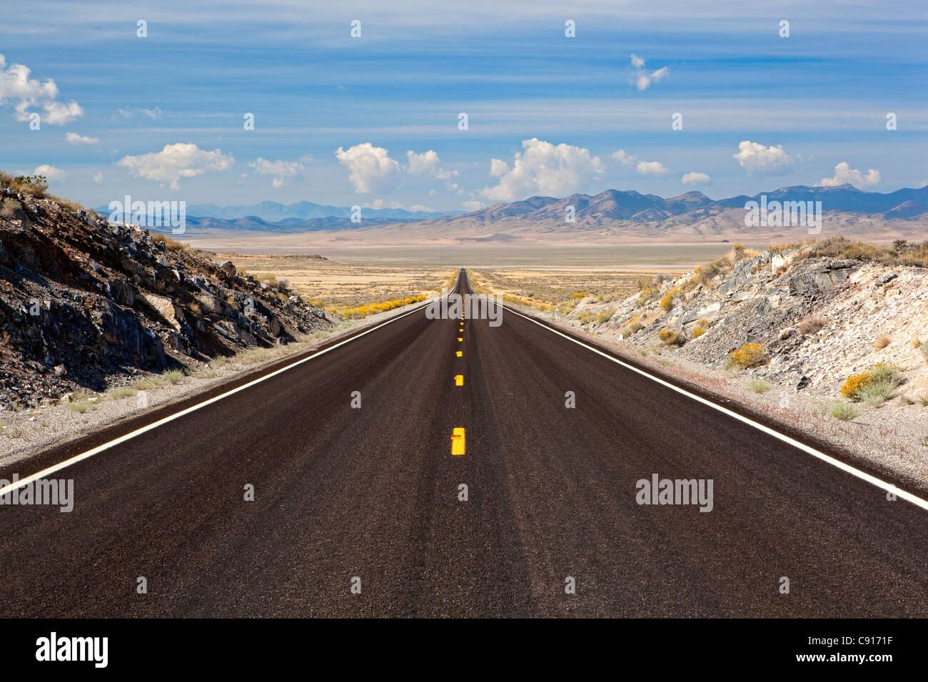 Eine langen gerade Straße, dachte die Wüste einige Berge in Nevada, USA Stockbild