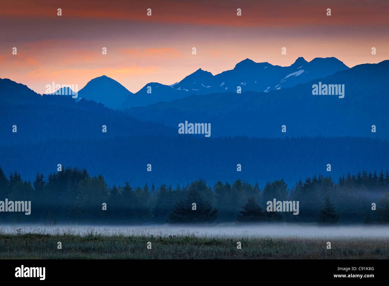 Malerische Landschaft der Berge bei Sonnenaufgang und Nebel über dem Boden, Glacier Bay Nationalpark & Stockbild