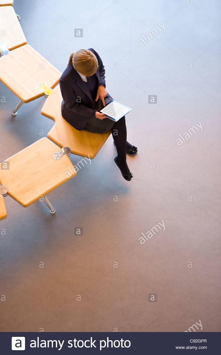 Studentin in Schuluniform, mit digital-Tablette auf Bank Stockbild