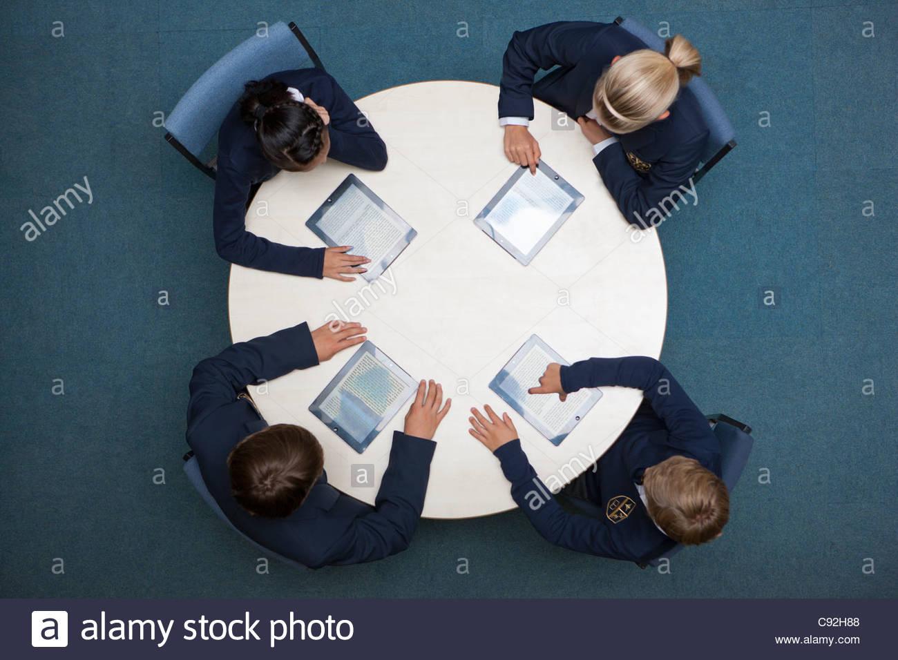 Schüler in Schuluniformen mit digitalen Tabletten am runden Tisch Stockbild