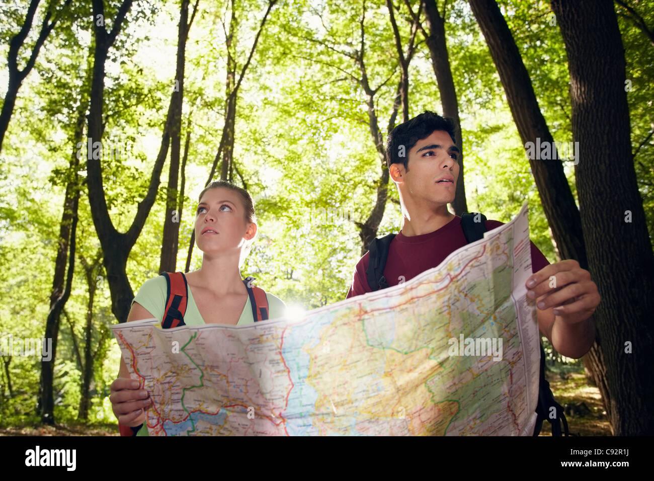 junger Mann und Frau verloren gegangen, während Wanderausflug und Ziel auf Karte suchen. Horizontale Form, Stockbild