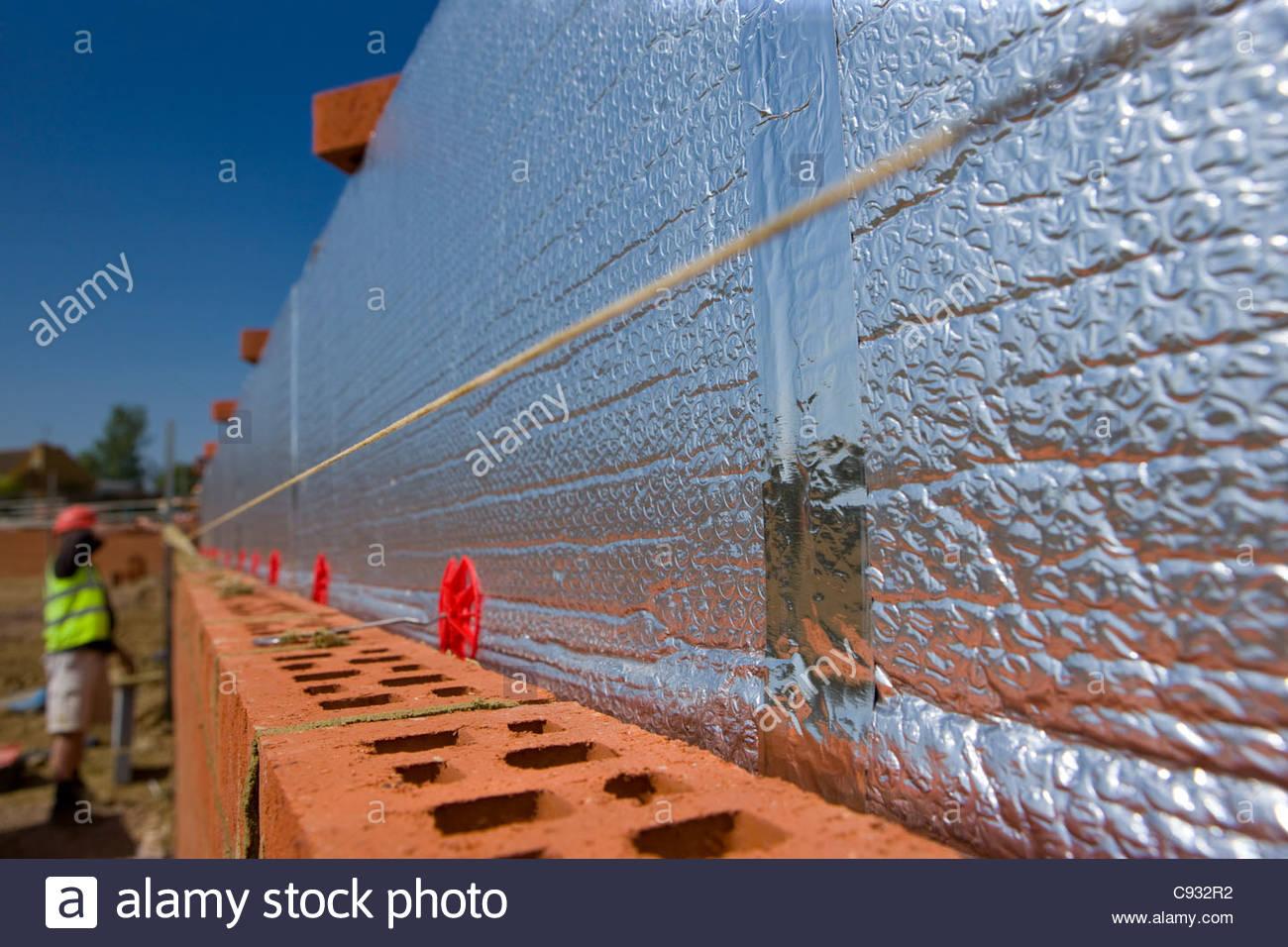 Isolierung auf Ziegelwand mit Maurer im Hintergrund Stockbild