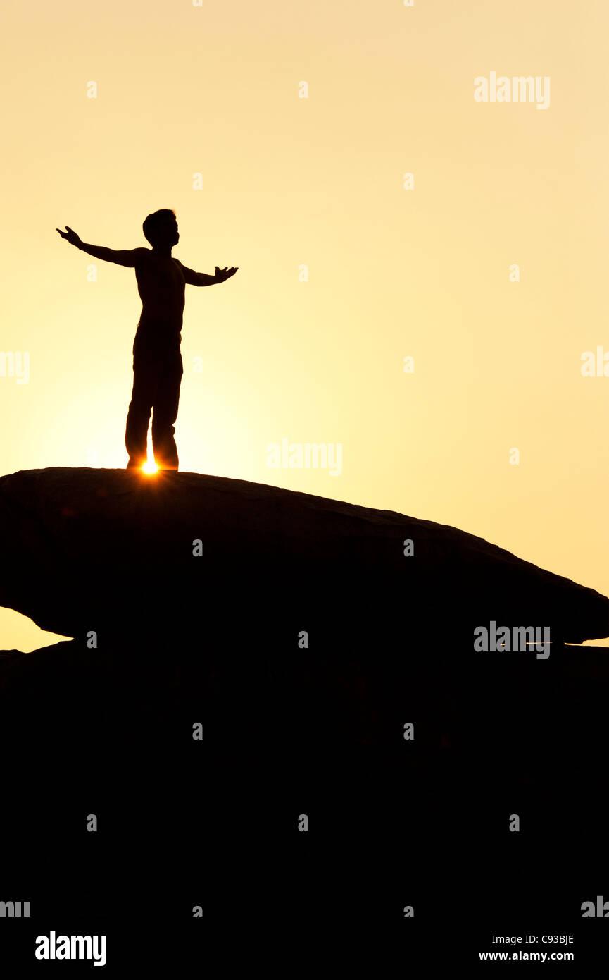 Indischer Mann auf einem Felsen umarmt die Sonne steht. Silhouette. Indien Stockbild