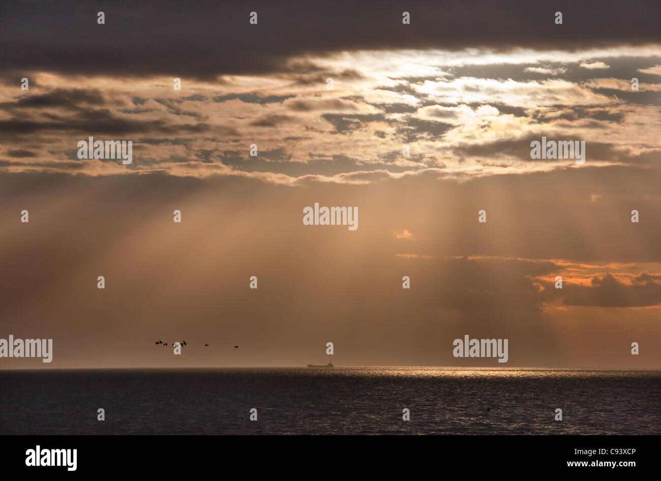 Die untergehende Sonne über dem Waschen Hunstanton Norfolk Stockbild