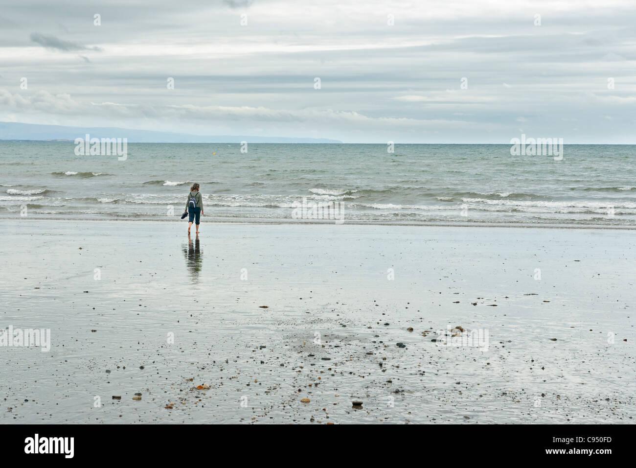 Frau am Criccieth Strand in Wales, UK Stockbild