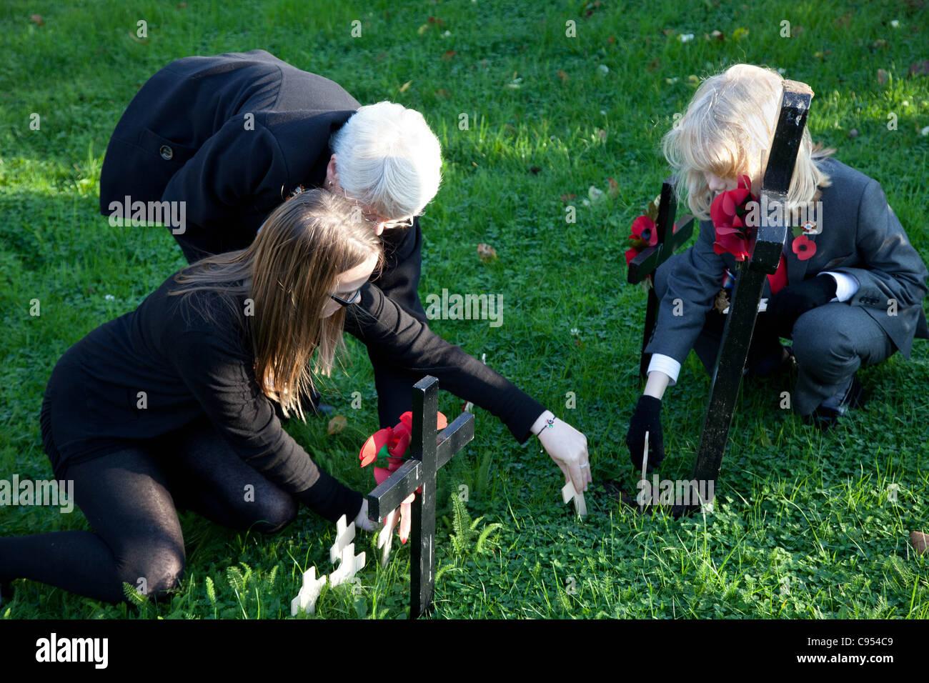 Familienmitglieder erinnern ein Soldat, indem man ein Kreuz in den Boden am Remembrance Day Sonntag Stockbild