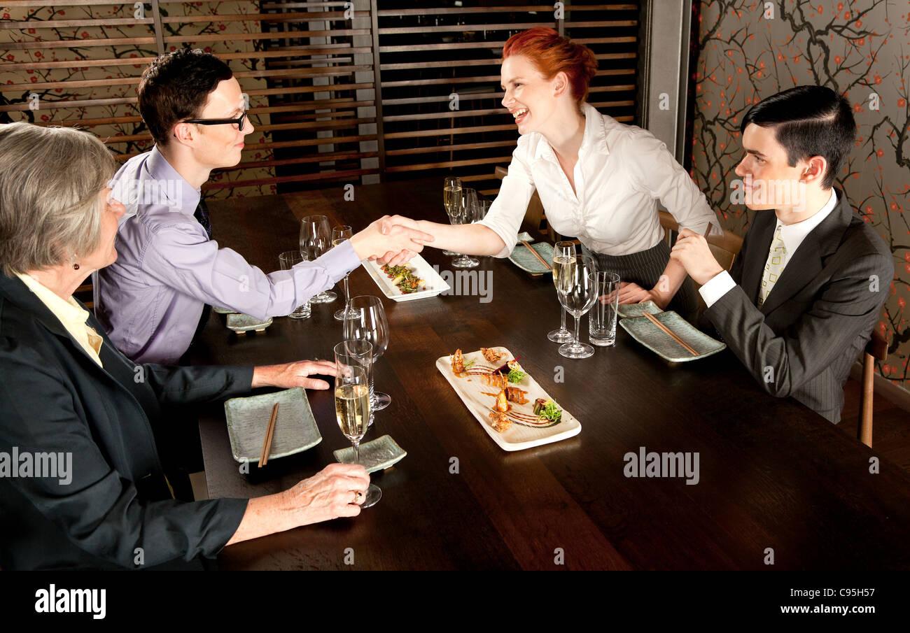 Vier Menschen treffen zum Mittagessen Stockbild