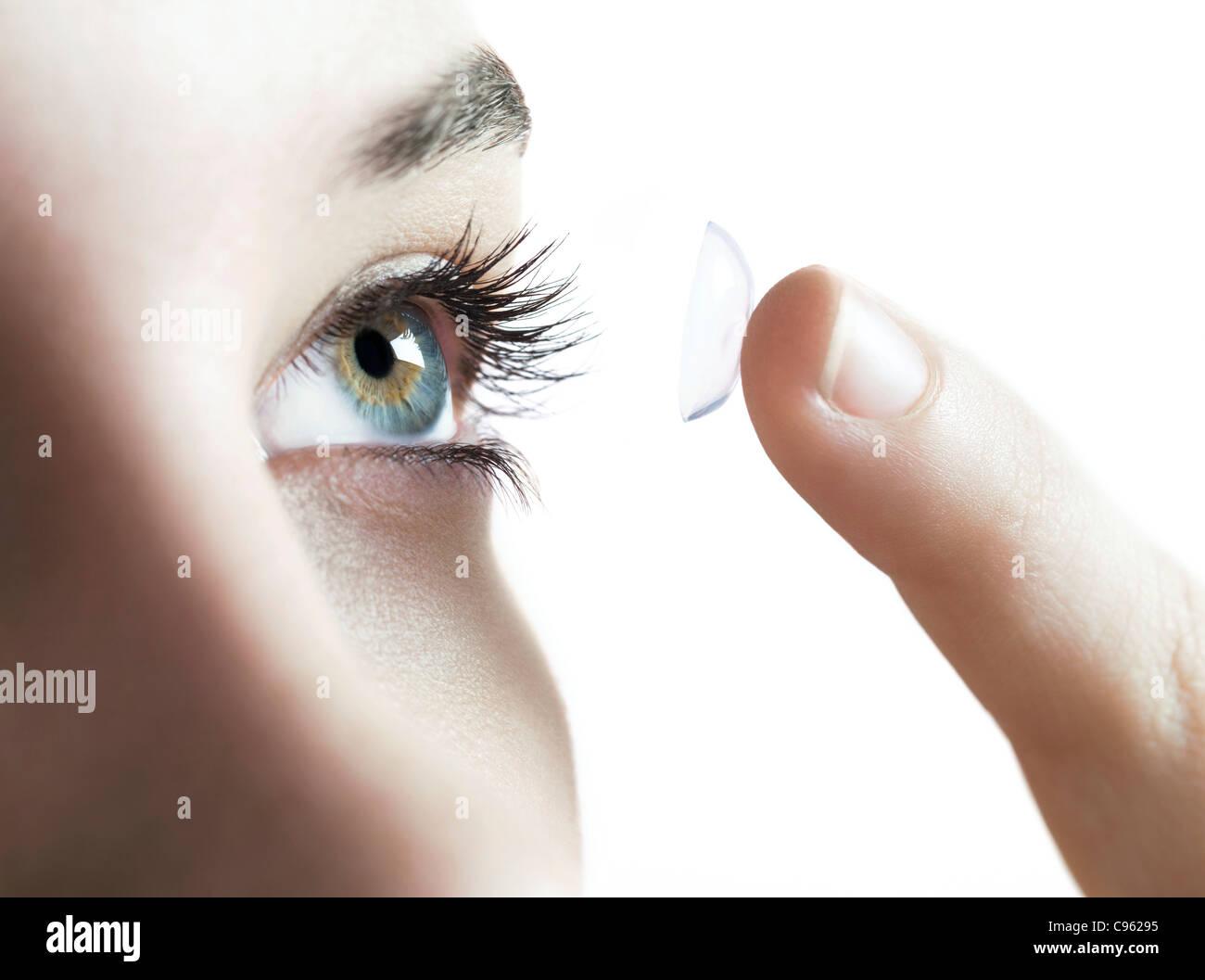 Kontakt-Objektive verwenden. Frau in einer Kontaktlinse weglegen. Stockbild
