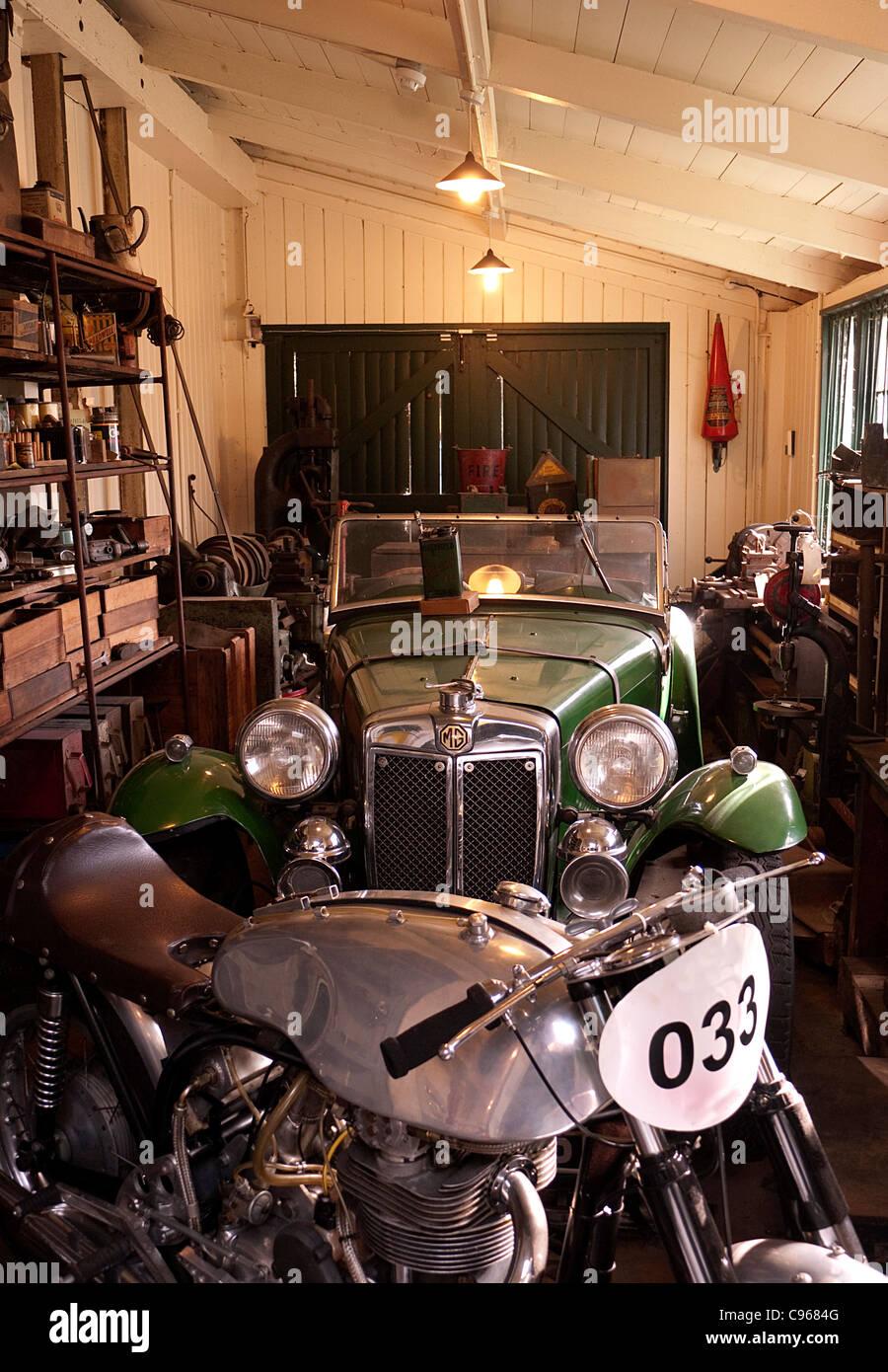 Oldtimer-Garage mit 30er Jahre MG Auto und Motorrad Stockbild