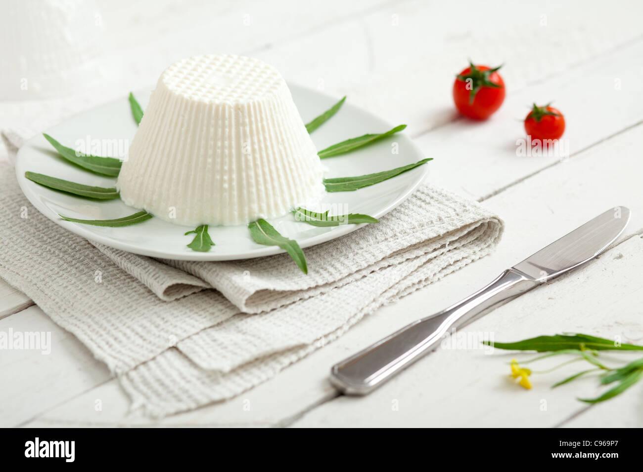 Ricotta, ein typisch italienisches Milchprodukt mit Rucola, Kirschtomaten und einem Messer Stockbild