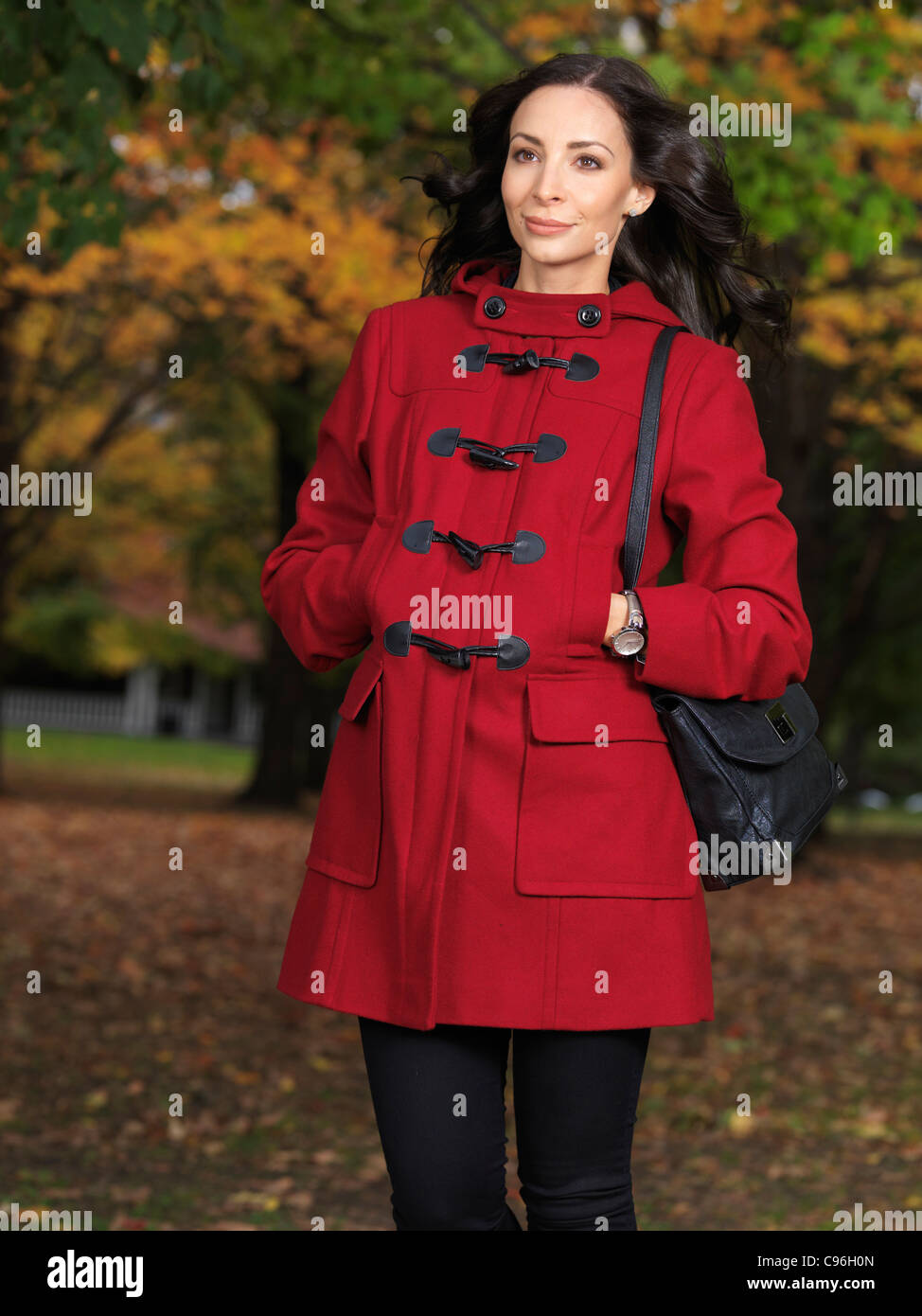 Schöne junge Frau auf der Straße im Herbst Natur trägt einen roten Mantel Stockfoto
