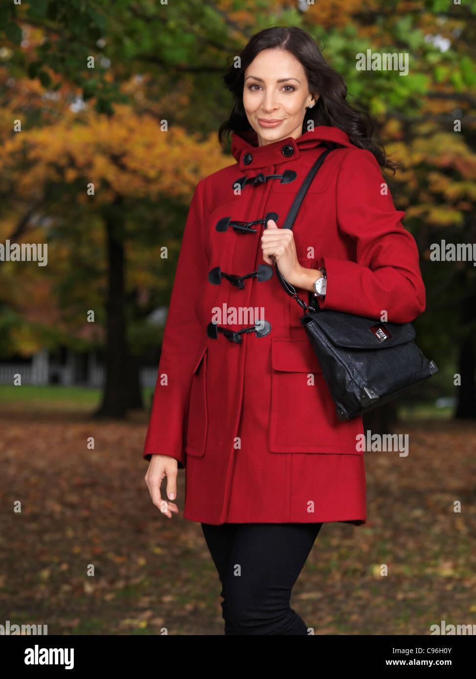 Schöne junge Frau trägt einen roten Mantel Stand auf einer Stadtstraße im Herbst Stockfoto
