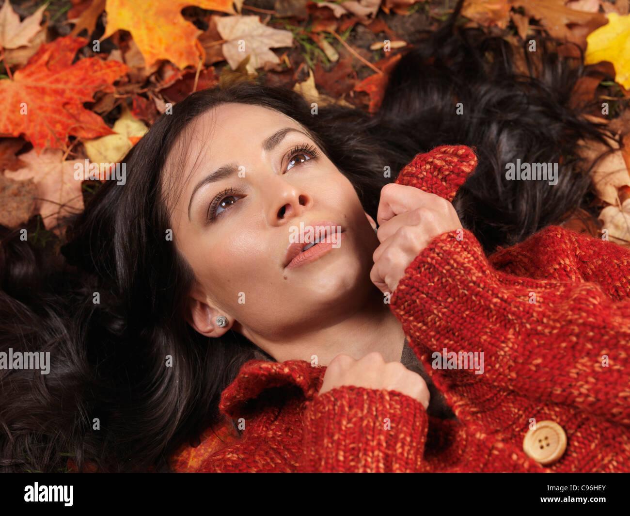 Schöne Frau mit verträumten Ausdruck auf bunten Laub liegend Stockbild