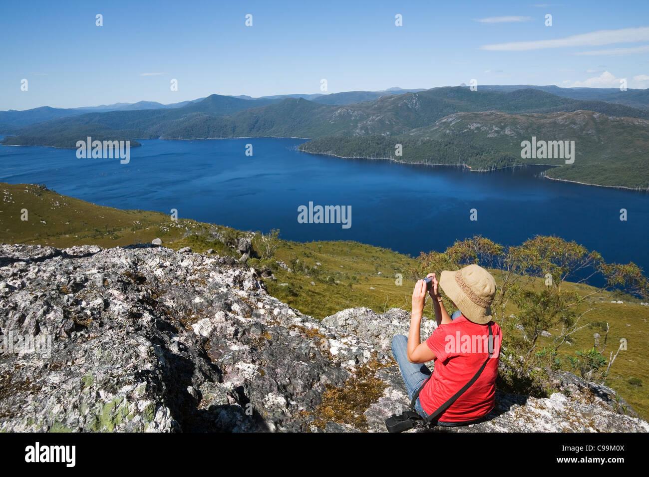 Ein Wanderer Fotografien Lake Mackintosh von oben auf Mount Farrell, im westlichen Hochland Tasmaniens. Tullah, Tasmanien, Australien Stockfoto