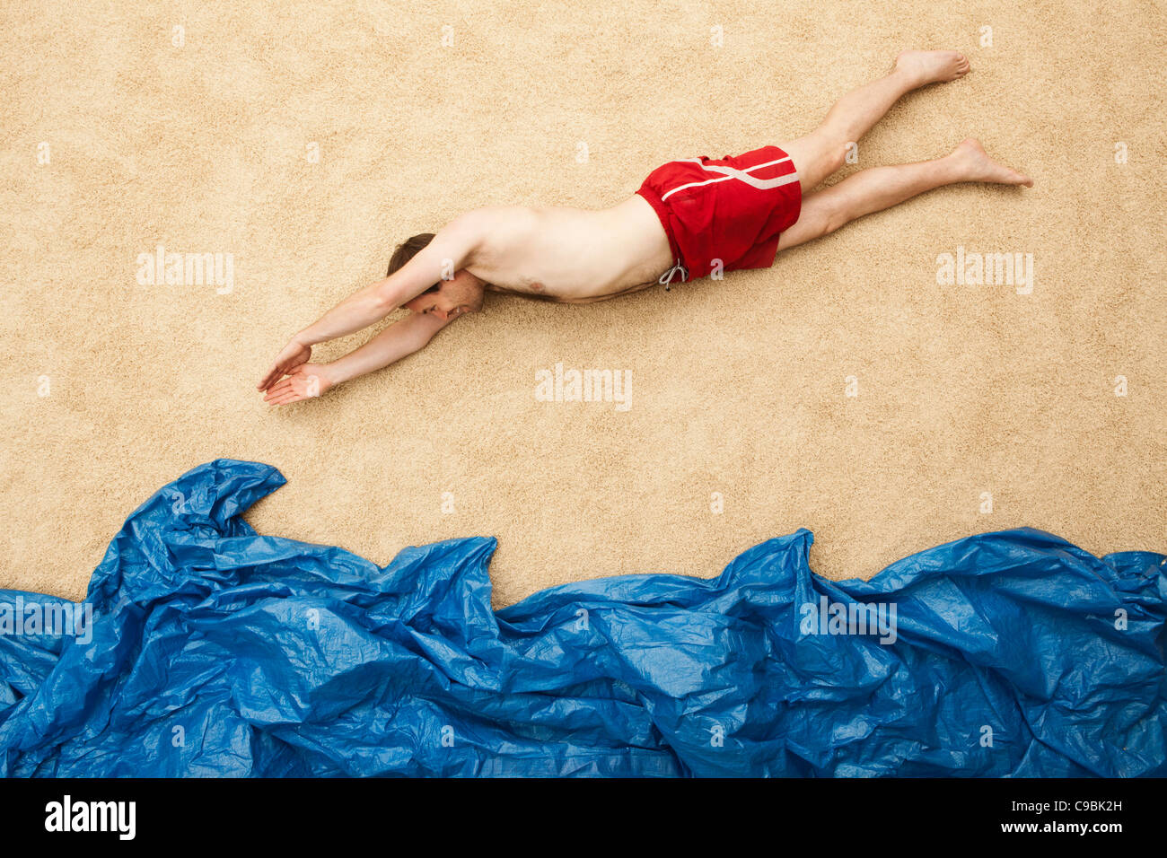Deutschland, junger Mann springt im Wasser am Strand Stockfoto
