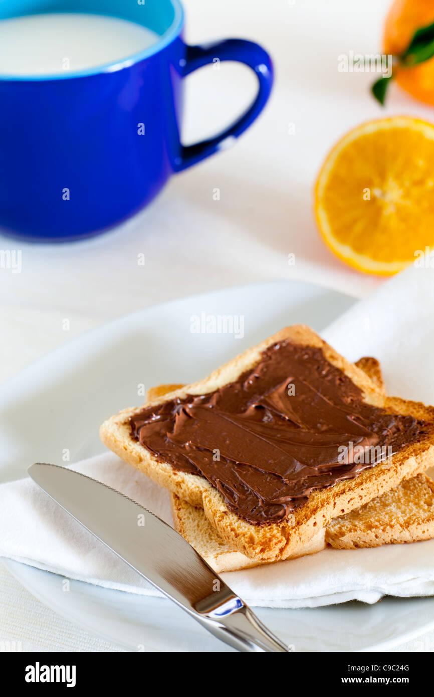Frühstück mit Nutella auf Toast, Milch und Orange Stockbild