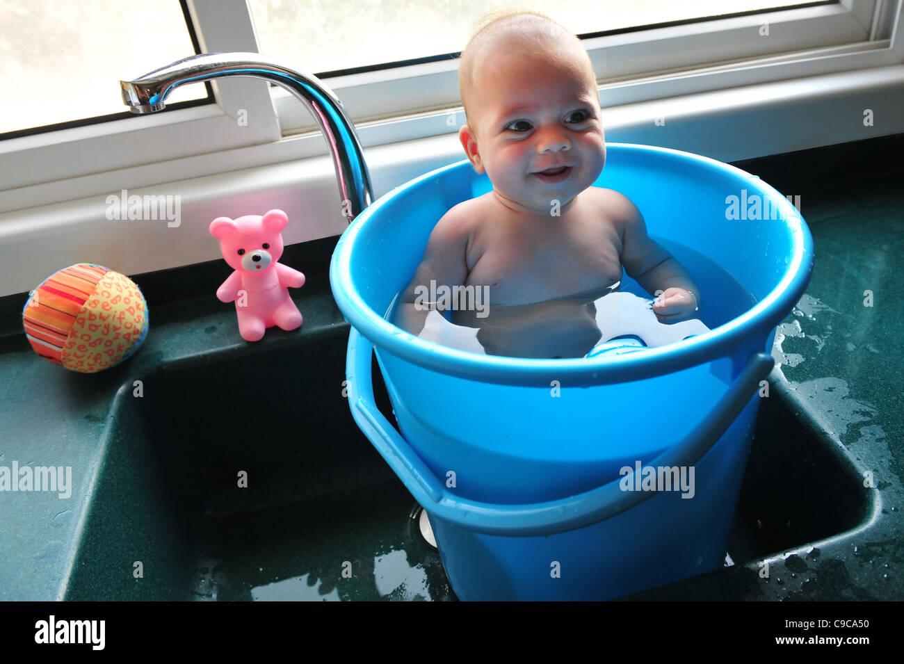 Ein Baby in einem blauen Eimer kühlt sich in der Hitze des Sommers Stockbild