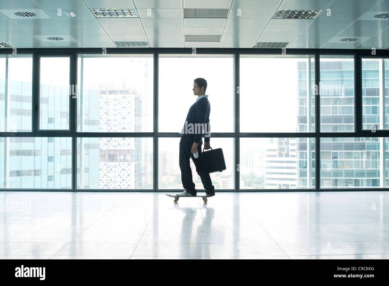 Geschäftsmann, stehend auf Skateboard mit dem Aktenkoffer Stockbild