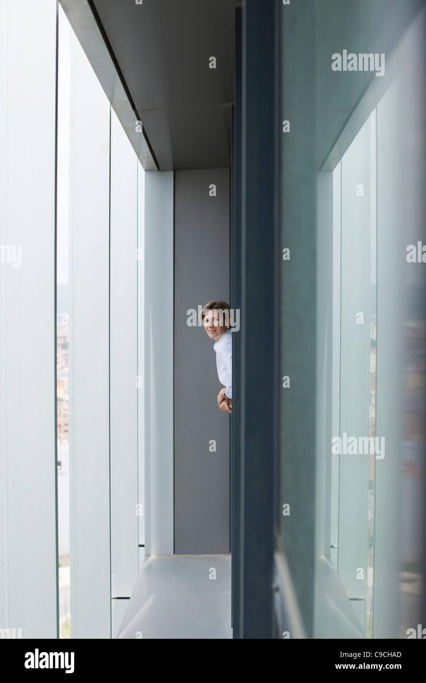 Frau aus Bürofenster gelehnt Stockbild