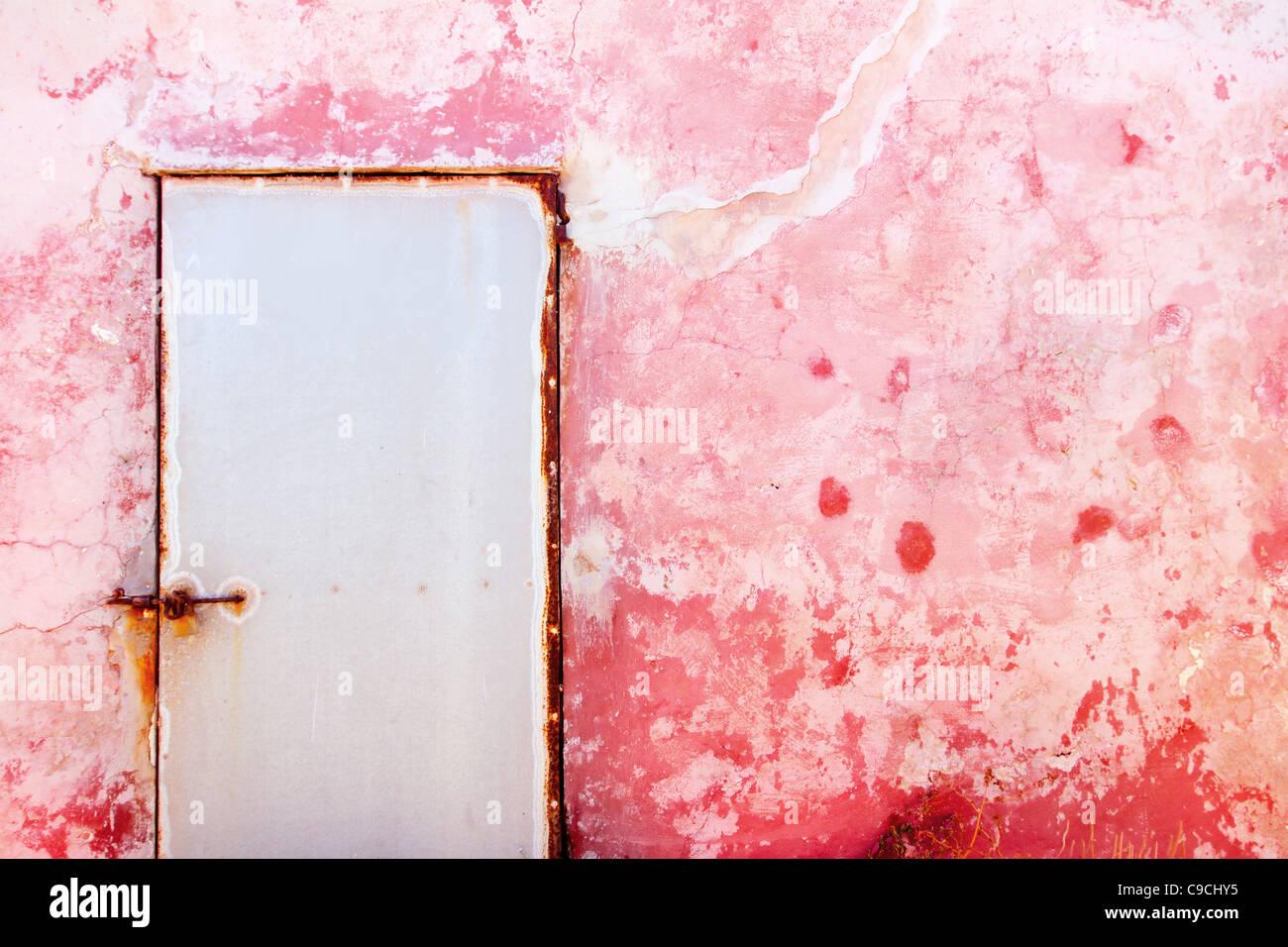 Rosa mediterrane Grunge Tür und Wand mit verwitterten Textur Stockbild